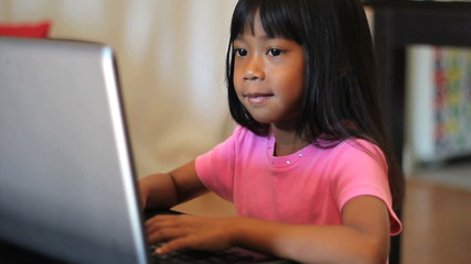 Little Girl Playing Games On A Lap Top