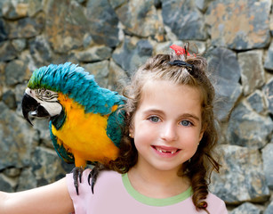 blue eyes child girl with yellow parrot
