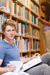 Portrait of a handsome student posing with a book while his clas