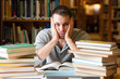 Leinwanddruck Bild - Depressed student having a lot to read