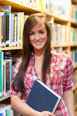 Portrait of a smiling female student holding a book