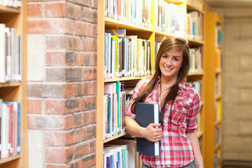 Cute young female student holding a book