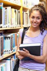 Portrait of a smiling female student posing with a book