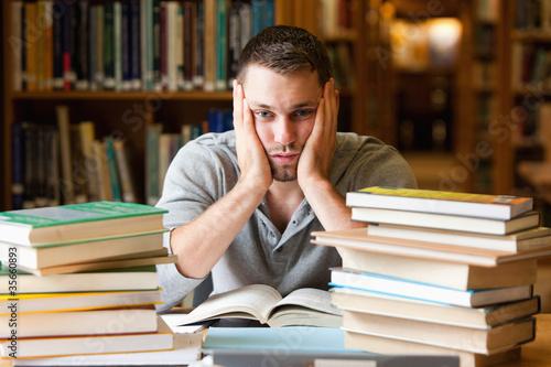 Leinwanddruck Bild Depressed student having a lot to read