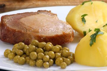 eine Scheibe Schweinebraten mit Erbsen und Salzkartoffeln