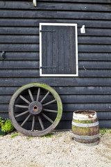 Wooden house, the old wooden wheels and wooden barrel.