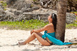 Beautiful woman sitting under palm tree at caribbean sea