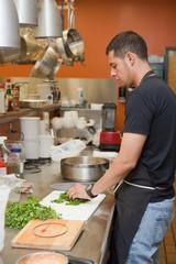 Sous chef preparing cilantro in professional kitchen
