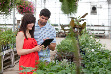 Couple with Digital Tablet in Greenhouse
