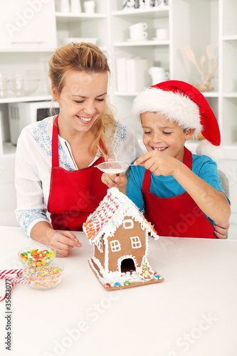 Final touches on the gingerbread house - people at christmas tim