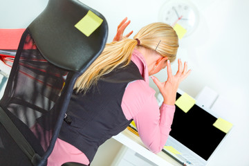 Business woman sitting at workplace covered with sticky