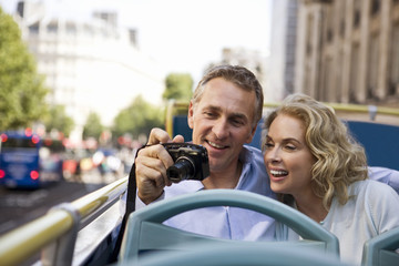 A couple sitting on a sightseeing bus, holding a camera