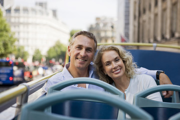 A couple sitting on a sightseeing bus, embracing