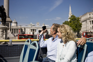 A couple sitting on a sightseeing bus, taking photographs