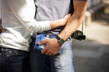 A couple holding a guidebook and a map of London