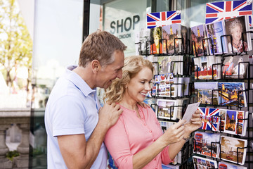 A couple looking at postcards outside a souvenir shop