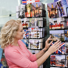 A woman looking at postcards outside a souvenir shop
