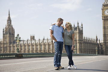 A couple standing near the Parliament, embracing