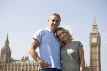 A couple standing in front of Big Ben, arm in arm