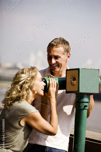 A middle-aged couple using a telescope, laughing