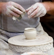 Artisan make a small potter from white clay.