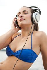 attraktive junge Frau im Bikini hört Musik
