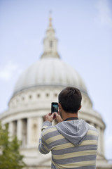 A man taking a photograph of St Paul's cathedral