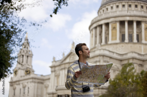 A man standing in front of St Paul's cathedral, looking at a map