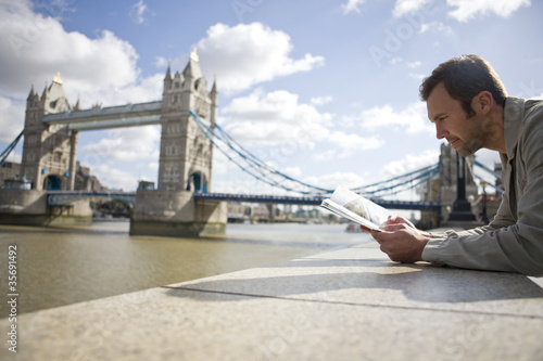 A man near Tower Bridge, looking at a guidebook