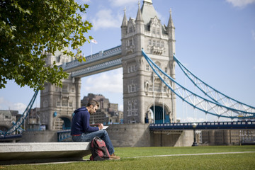 A man sitting near Tower Bridge, writing a postcard