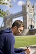 A man sitting near Tower Bridge, writing a postcard