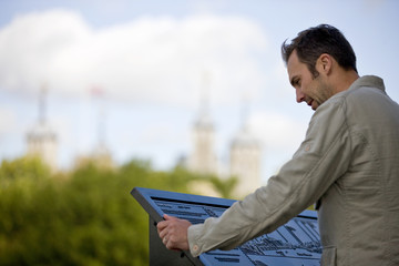 A man in front of the Tower of London, looking at a map