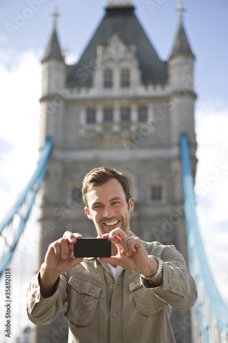 A man taking a photograph of himself in front of Tower Bridge