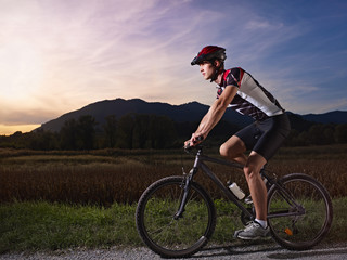 young man training on mountain bike at sunset