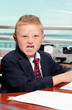 Cute boy with angry face in business attire in an office
