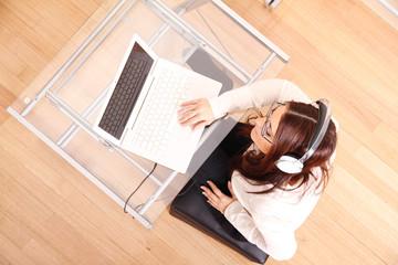 Frau mit Laptop und Kopfhörern
