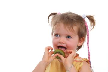 Kleine Mädchen schleckt Kiwi/ V