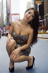 Fashion Model Kneels on Crowded City Street
