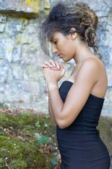 Femme priant les mains jointes et les yeux fermés.