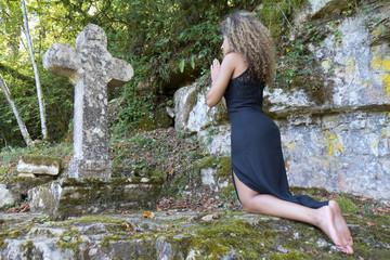 Femme priant à genoux et pieds nus