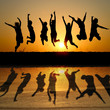 silhouette of friends jumping in sunset with reflection