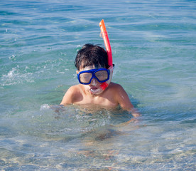 Swimming boy with snorkel mask in the sea