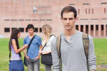 Lonely male student posing while his classmates are talking