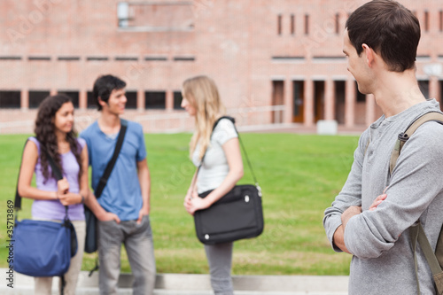 Student looking at his classmates talking