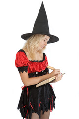 teenager girl in Halloween witch reads magic book