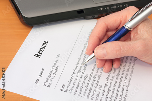 Hand with Pen Proofreading a Resume by Laptop