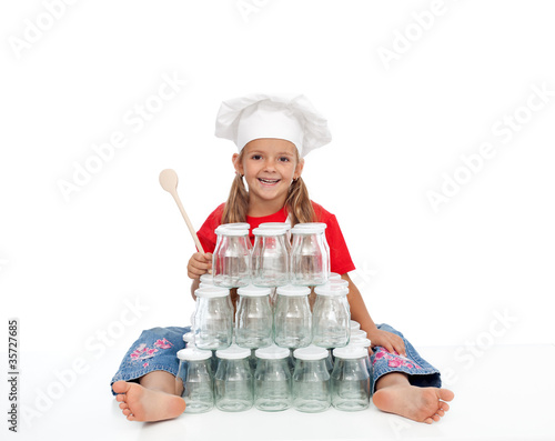 Happy chef girl with jars for canning
