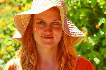 young woman's face under straw hat
