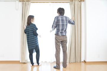 カーテンを開く若い男女のカップル