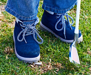 boy shoes and golf club on grass